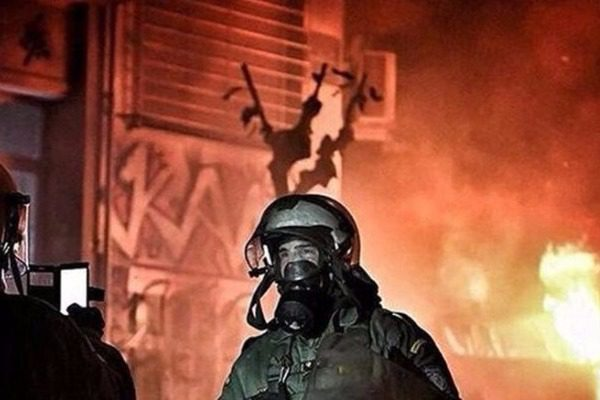 Ανδρας των ΜΑΤ πόζαρε με φόντο τις φωτιές στα Εξάρχεια